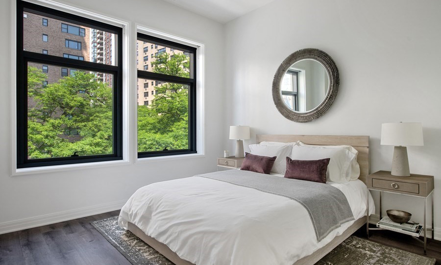 A modern bed with an end table and lamp on each side and mirror over the head board in a bedroom at 61 Banks Street. Two windows are on the left with green trees seen outside.