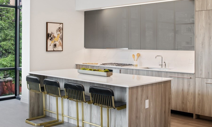 A kitchen counter with stools faces the kitchen with custom, European cabinetry.