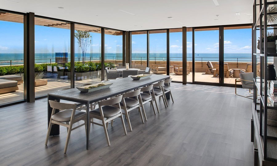 A long dinging room table sits in a open room with floor-to-celing windows. The sky terrace is seen outside and Lake Michigan beyond on a sunny day.